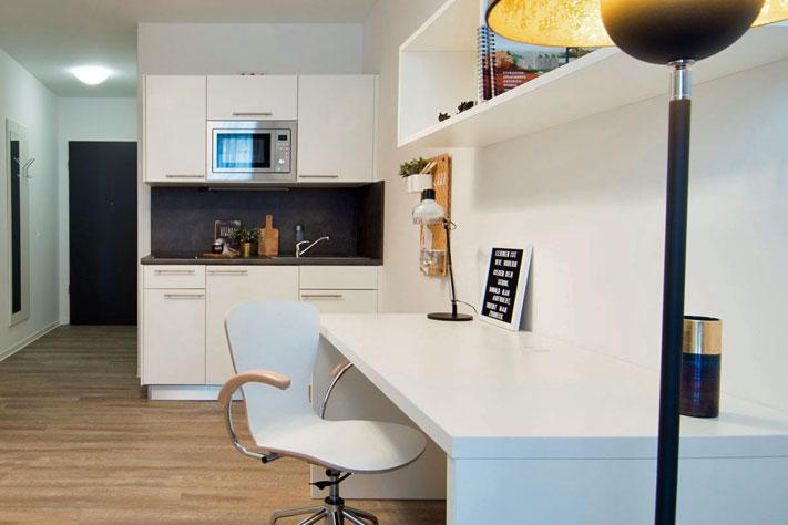 Apartment der 2CP Cube Capital Partners mit Schreibtisch, Lampe und Küchenzeile